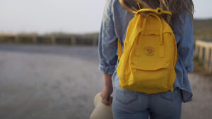 Fjallraven Kanken backpack review: feature image of girl with yellow bag