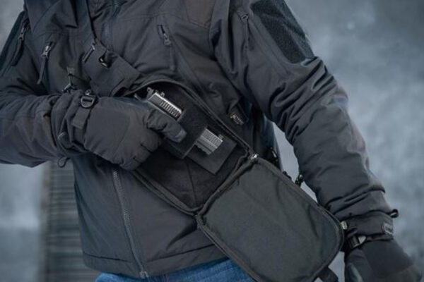Best concealed carry: a man drawing out a gun from a backpack