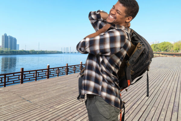 Best backpacks for back pain - feature image of man who appears to be in pain wearing his backpack